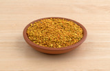Small bowl of bee pollen granules on a wood table.