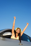 Happy successful woman raising arms from the car window. Freedom, driving goals and roadtrip concept.