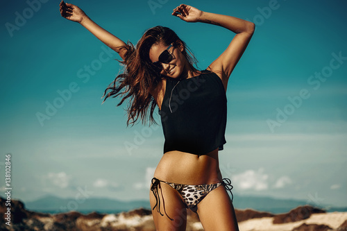 Beautiful party girl dancing and waving hands on the beach over blue sky