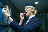 Blonde hair stewardess colors red lipstick at the airport