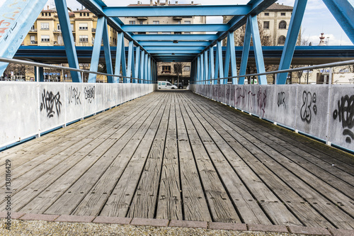 Fototapeta Blue iron bridge on a wooden floor