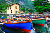 Pictorial scenery with boats in beautiful lake Lago di Garda. Torbole village. Italy