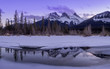 Sunset view of the Three Sisters from a frozen Policemen's Creek along the Bow River outside Canmore, Alberta in winter.