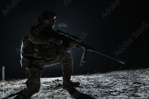 Army sniper with big rifle sitting holding rifle on black background Poster