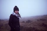 Mujer joven caminando en la niebla