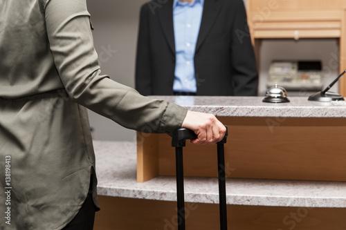 Frau steht an Rezeption von einem Hotel, Gast beim Einchecken
