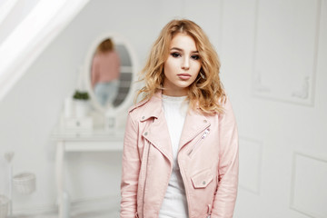 Young beautiful woman in fashionable pink jacket on a light background