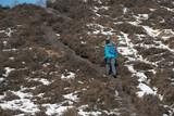 Man walking uphill in winter landscape.