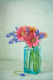 Beautiful spring flowers in a blue vase .Green textured background.