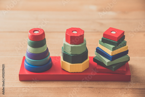 Poster stack of many shape cube building blocks on wooden table , children toy