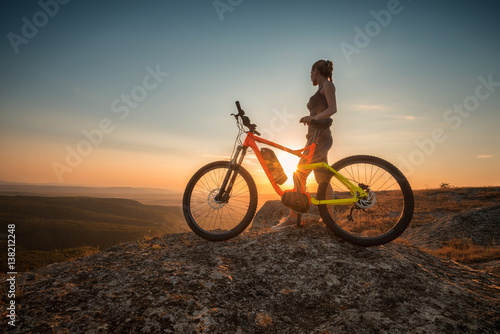 Active life / A woman with a bike enjoys the view of sunset over an autumn forest