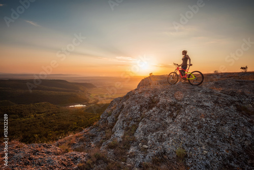 Tuinposter Chocoladebruin Active life / A woman with a bike enjoys the view of sunset over an autumn forest