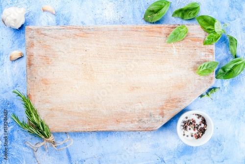 Food background: a cutting board on a light blue stone concrete table with spices and herbs for cooking - garlic, rosemary, basil, salt, pepper. Italian style