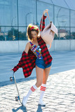 Stylish girl with a skateboard on the street
