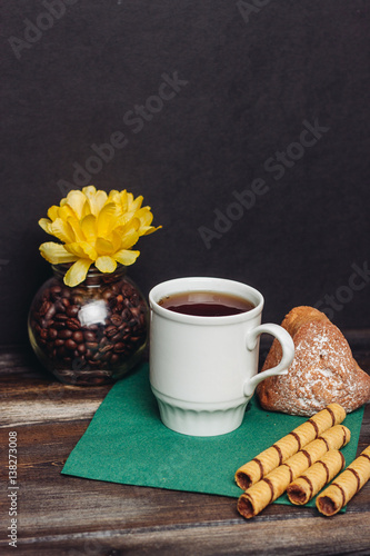 a jar with coffee beans, a mug with a drink and flour products on a green napkin © ageevphoto