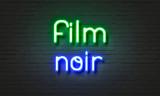 Film noir neon sign on brick wall background.
