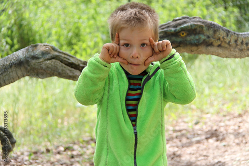 Poster Little boy with hands by his eyes with the dinosaurs in behind