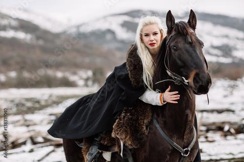 Beautiful blonde Viking in a black cape on horseback Poster