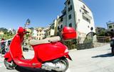CORNIGLIA, ITALY - APR 14: Red vintage Vespa in the city streets, April 14, 2013 in Corniglia, Italy. This is the preferred way to travel in the Cinque Terre Park