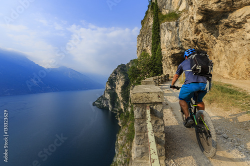 Poster Mountain biking at sunrise man over Lake Garda on path Sentiero della Ponale, Ri