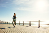 Healthy woman running on the sea side promenade