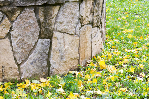Foto op Aluminium Op straat Texture, pattern, background. Autumn leaves, Granite stones. Sandstone, put a fence flowerbeds. sedimentary rock consisting of sand or quartz grains cemented together, typically red, yellow,