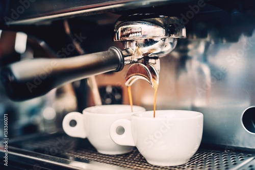 Proffessional brewing - coffee bar details. Espresso coffee pouring from espresso machine. Barista details in cafe