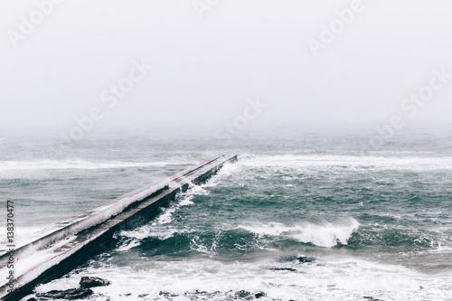 Concrete pier during snowfall, gloomy landscape - 138370477