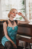 Beautiful woman actress in retro dress sitting at the piano