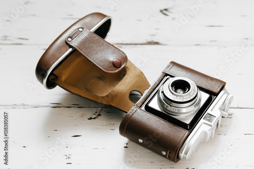 Poster Old film camera in brown vintage case  on white wood background
