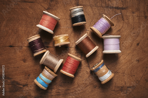 Póster vintage spools of thread on a distressed wood surface