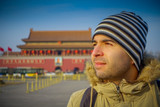 BEIJING, CHINA - 29 JANUARY, 2017: Hispanic tourist on Tianmen square looking around, famous forbidden city building in background, beautiful blue sky