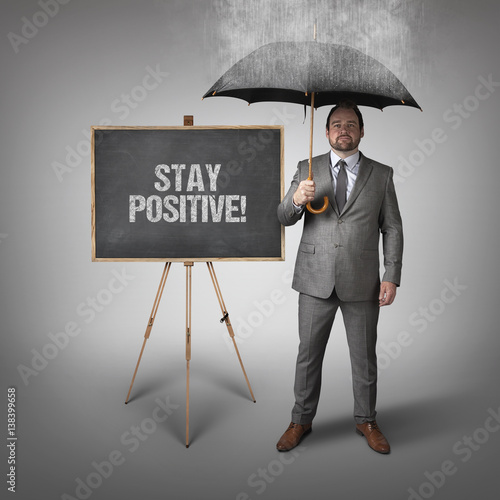 Poster Stay positive text on blackboard with businessman