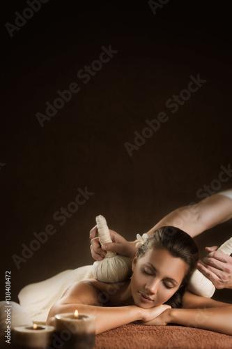 Piękna dziewczyna ma masaż ziołowymi piłkami. Luksusowy zabieg spa. Szablon projektu do umieszczania tekstu.