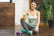 Cheerful beautiful young fitness woman sitting on wooden floor at home with detox and dumbbells. Relax after work-out. Sport concept on wooden dark floor. Top view.