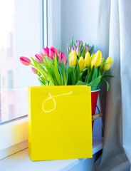 bunch of beautiful colorful tulips in red bucket  and cool shopping bag on the wonderful windowsill