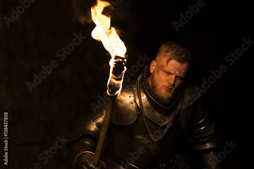 Knight with a torch at night on a wall background Poster