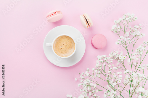 Morning cup of coffee, cake macaron and flowers on pink table top view in flat lay style Poster