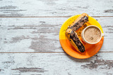 Coffee, cake, eclair with chocolate chips closeup on vintage wooden background. Top view.