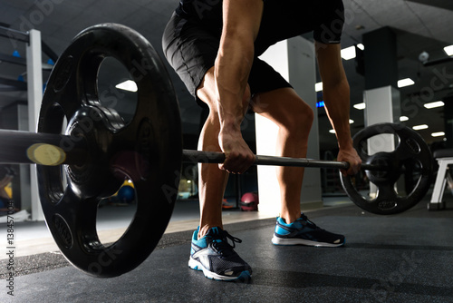Closeup of weightlift workout at the gym with barbell.