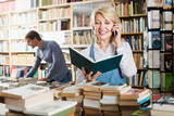 Woman looking at book and talking on mobile phone