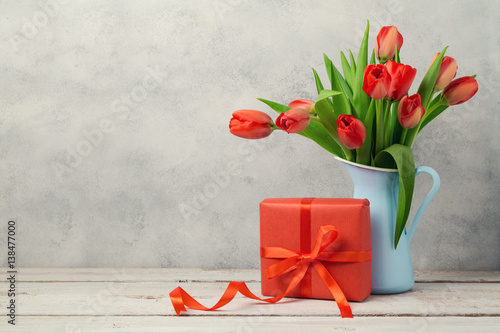 Red tulip flowers bouquet and gift box over rustic background. Women day or birthday celebration concept