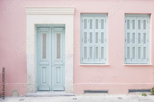Pastelowy różowy budynek i mlecznoniebieski drzwi otaczający marmurem w Ateny, Grecja