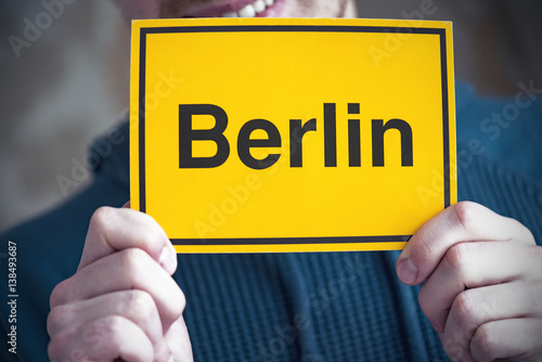 "Poster A tourist holding yellow postcard with the word ""BERLIN"""