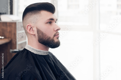 a young guy sitting on a chair in the barbershop. looking to the side