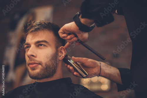 Handsome man at the hairdresser getting a new haircut