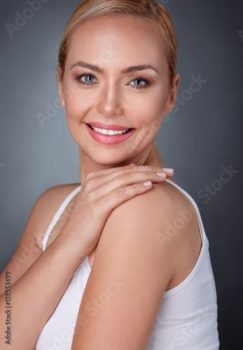 Leinwanddruck Bild Smiling middle aged woman touching skin