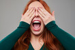Excited young woman with red hair covering eyes with hands