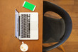 laptop on wooden table with coffee cup, phone  on top view with space in center