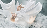 Attractive blond lady lying on pure white sheet